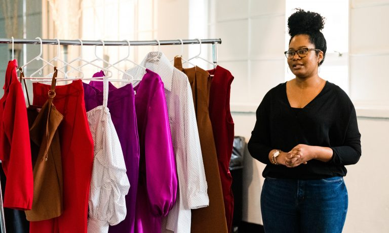 Picture of a women wearing a black shirt and jeans next to a clothing rack of red, white, brown, and pink clothing.