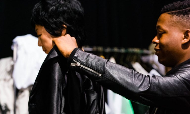 Picture of a man putting on a leather jacket on a model for fashion week prep