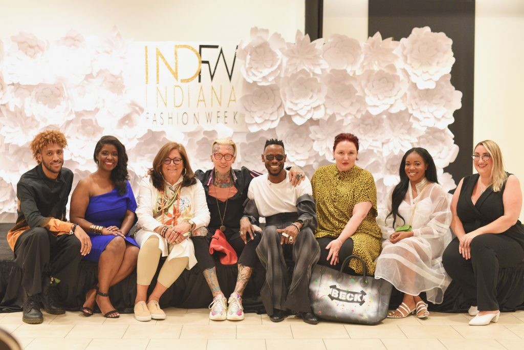 Picture of a group of 8 people sitting together taking a picture for Indiana Fashion Week