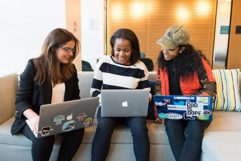 Three women sitting on a sofa with macbooks on their laps