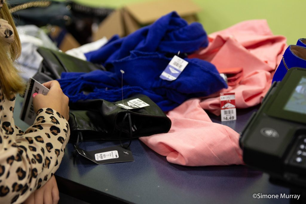 image of pile of clothing being scanned and check out during imagine IFF Youth Fashion Camp