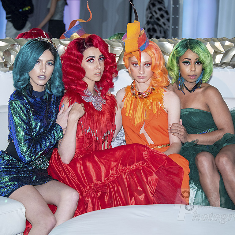 Four young women sitting down posing for a picture. (all wearing one color form head to toe) (from left to right colored worn, blue, red, orange, and green)