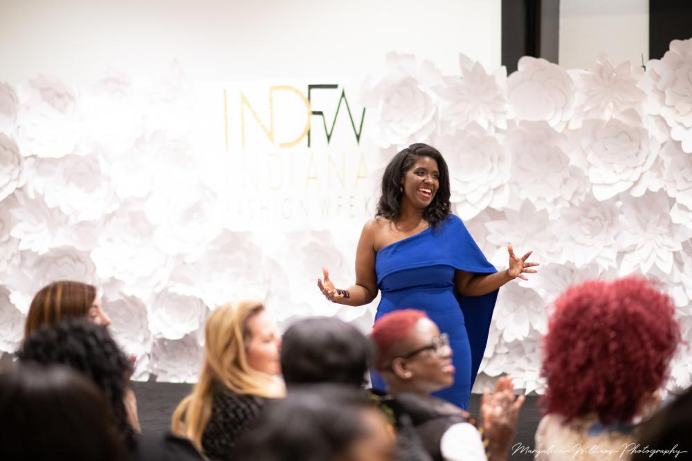 Women wearing a off the shoulder blue dress at Indiana Fashion Week in front of a group of people