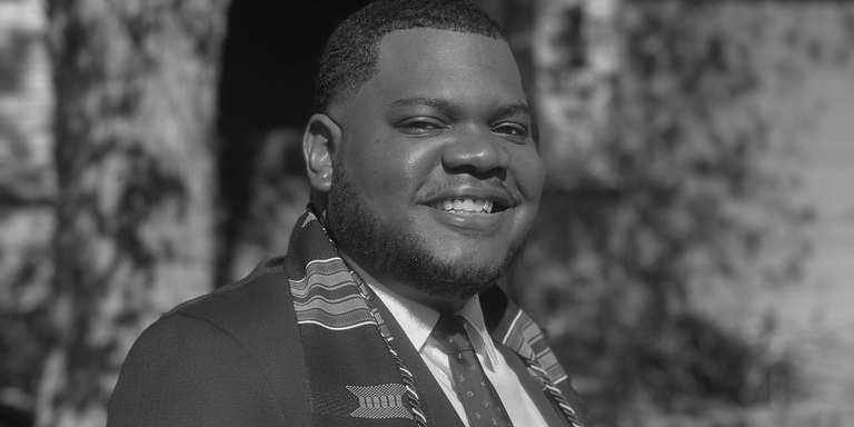 Picture of a young man smiling wearing a suit with Kente collegiate stole around his neck
